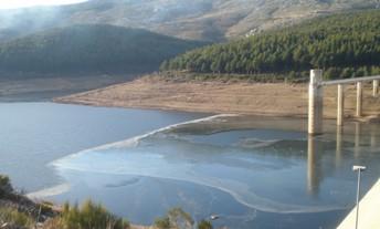 La presa de Navamuño sucumbe a los menos 14º centígrado de la madrugada del domingo y se hiela con una fina capa parte de sus aguas.
